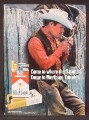 Magazine Ad For Marlboro Cigarettes, Cowboy Leaning On Old Fence, Saddle On Top, 1972