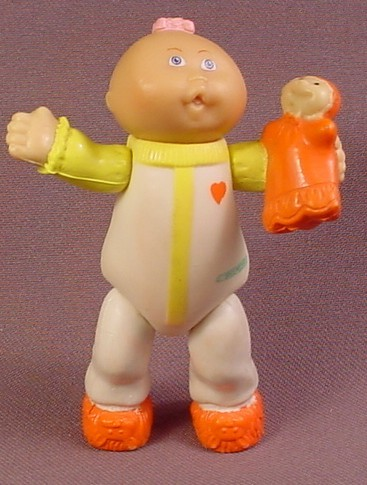 Cabbage Patch Kids Poseable PVC Figure In White & Yellow Pajamas Holding An Orange Doll